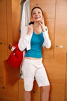Woman in locker room after work out talking on cell phone