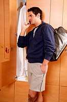 Man in locker room after work out talking on cell phone