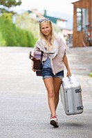 Austria, Teenage girl with wheeled luggage and guitar, portrait