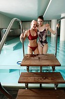 Two young women standing next to spa pool