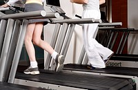 Young woman and man on treadmill, waste down