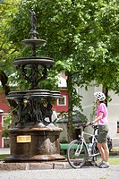 Austria, Salzburger Land, Mid adult woman standing by fountain