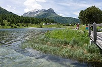 Switzerland, Mature man cycling by Lake Sils