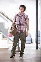 Germany, Bavaria, Young man standing with bag at home