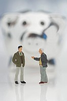 Male figurines with piggy bank on white background