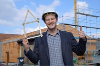 Germany, Bavaria, Young man with hard hat showing pocket rule and thumbs up at construction site