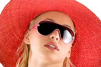 closeup portrait of pretty blond woman wearing a nice summer red hat and sunglasses
