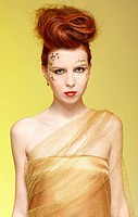 portrait of beautiful redhead girl in golden dress posing on yellow