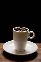 Nice image of an expresso cup and saucer with beans and a black background