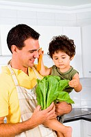 a father and son cooking a vegetarian meal in kitchen