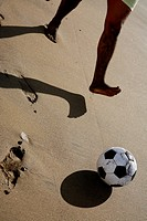 Football on sandy beach with player´s legs