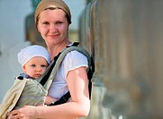 Lifestyle portrait of young mother and baby daughter in baby carrier outdoors