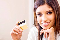 beautiful young woman holding a bank credit card and smiling