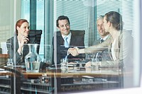 Business people shaking hands at table in conference room