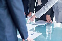 Businesswoman pointing to paperwork on table in meeting (thumbnail)