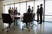 Separate groups of business people facing off in conference room (thumbnail)