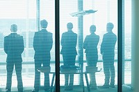 Silhouette of business people in a row looking out office window