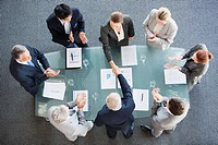 Business people shaking hands across conference room table