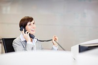 Smiling businesswoman talking on telephone in office