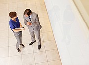 Businessman and businesswoman reviewing paperwork in corridor