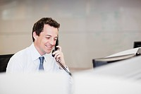 Smiling businessman talking on telephone in office (thumbnail)