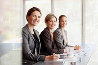 Portrait of smiling businesswomen sitting in a row in conference room (thumbnail)