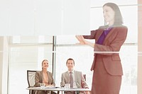 Businesswoman leading meeting on visual screen in conference room
