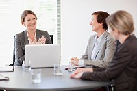 Smiling businesswomen with laptop meeting in conference room (thumbnail)