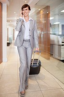Businesswoman talking on cell phone and pulling suitcase in corridor