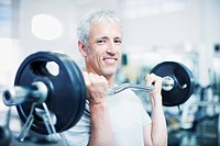 Portrait of smiling man holding barbell in gymnasium (thumbnail)