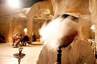 Ein Beduine raucht in der Cave Bar eine Wasserpfeife, dies im Dorf Wadi Musa bei der Historischen Felsstadt Petra im Sueden von Jordanien
