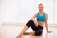 Portrait of smiling woman in sports bra sitting on floor (thumbnail)