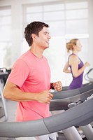 Smiling man running on treadmill in gymnasium