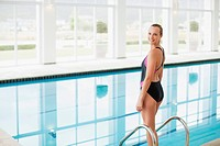 Portrait of smiling woman standing at edge of swimming pool