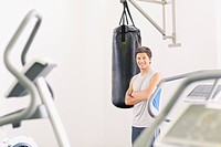 Portrait of smiling man standing at punching bag in gymnasium