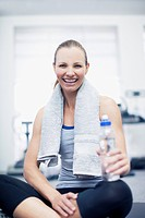 Portrait of smiling woman sitting with towel and water bottle in gymnasium
