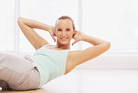 Portrait of smiling woman doing sit_ups