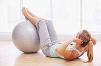 Woman doing sit_ups with fitness ball