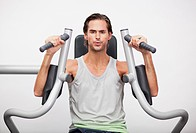 Portrait of man using exercise equipment in gymnasium