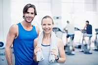 Portrait of smiling man and woman in gymnasium
