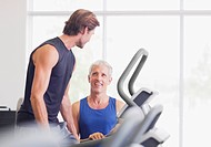 Men talking on treadmill in gymnasium