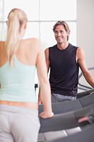 Man and woman talking on treadmills in gymnasium