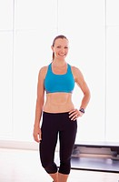 Portrait of smiling woman wearing sports bra in fitness studio