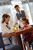 Waiter serving coffee and cake to a mother and her daughter in a café