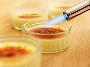 Flame from torch burning sugar on crème brulee
