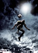 afrcican soccer player heading a ball in a stormy weather