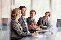 Smiling business people meeting at table in conference room