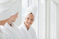 Women in bathrobes and hair wrapped in towels at spa