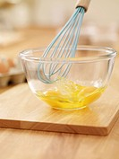 Wire whisk beating eggs in bowl on cutting board