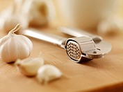 Close up of garlic and garlic press on cutting board
